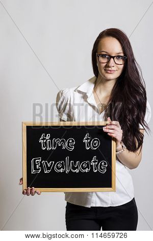 Time To Evaluate - Young Businesswoman Holding Chalkboard
