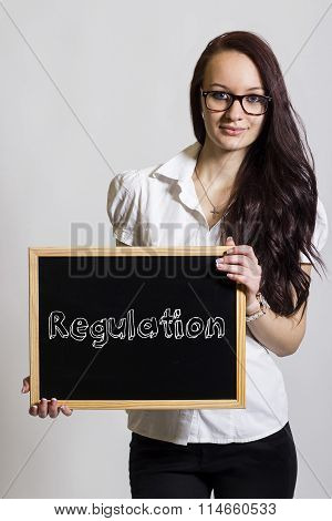 Regulation - Young Businesswoman Holding Chalkboard