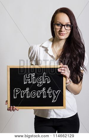 High Priority - Young Businesswoman Holding Chalkboard