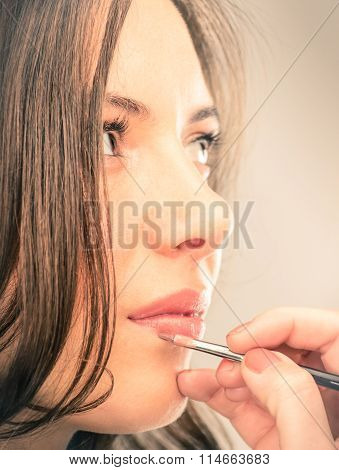 Make-up Artist Refining Lips Of A Beautiful Young Model
