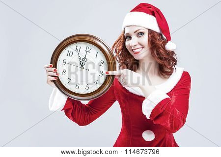 Time Concept And Ideas. Gleeful Red-haired Santa Helper With Big Round Clock And Showing Time. Posin
