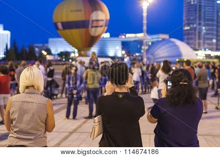 Minsk-Belarus, July 19, 2015: Three Girlfriends Taking Pictures Of Air-balloons During Night Show An