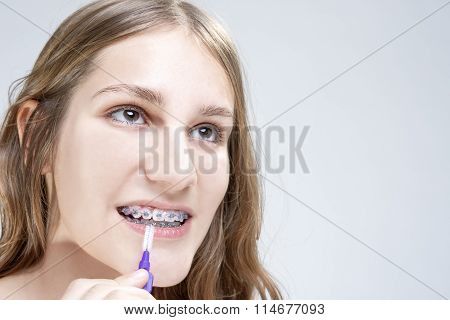Dental Hygiene Concepts. Caucasian Teenage Girl Using Bristle Teeth Brush For Brackets