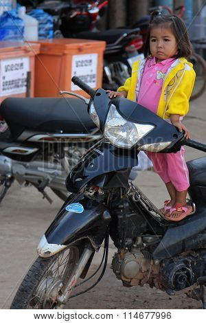 Stung Treng, Cambodia, November 25, 2012 : A Little Girl Waits On A Bike For Her Mother At The Marke