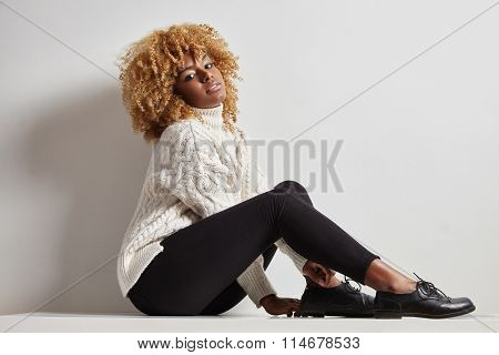 Blondy Black Woman With A Curly Hair Sitting In A Knitted Jersey