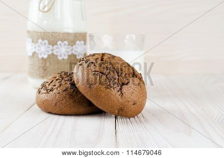 Brown Rolls With Caraway Seeds. Milk And A Glass Jar.
