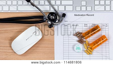Wooden Desktop With Blank Patient Medication Form Plus Capsules With Their Containers