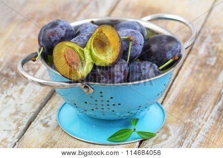Fresh plums in blue colander on rustic wooden surface