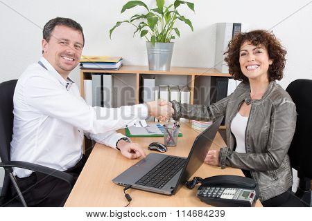 Confident Businessman Shaking The Hand Of A Brunette Interviewee In Office