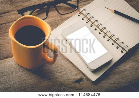 Yellow Coffee Cup With Book Eyeglass Notebook Smart Phone And Pencil On The Wooden Table - Tone Vin