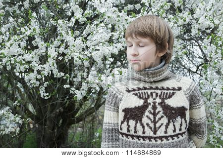 Daydreaming teenage boy with closed eyes wearing knitted wooly reindeer warm sweater outdoors at flo