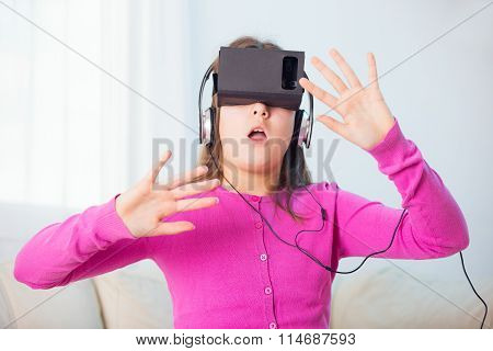 Happy smiling young beautiful young girl getting experience using VR-headset glasses