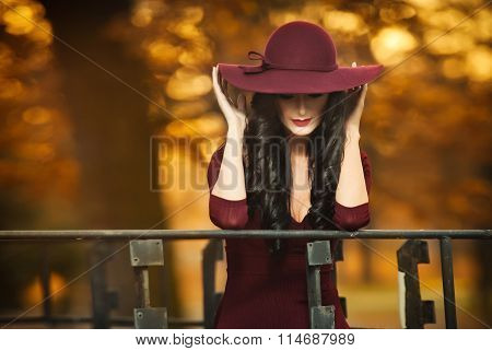 Attractive young woman with burgundy colored large hat in autumnal fashion shot