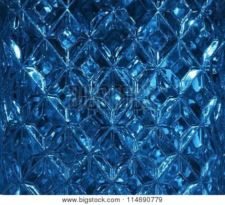 Dark blue glass texture with a pattern of rhombuses. Clear glass diamond shape. Crystals. Closeup