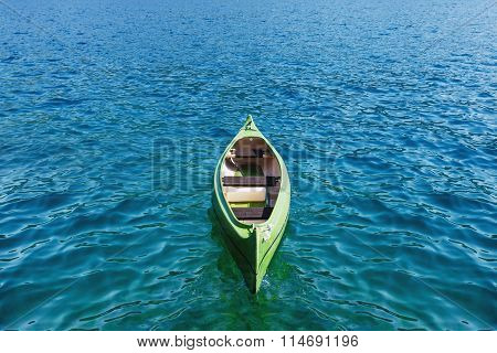 Canoe floating on the transparent sea water.