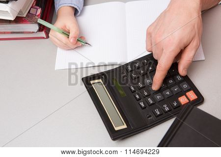 Man pushing buttons on calculator