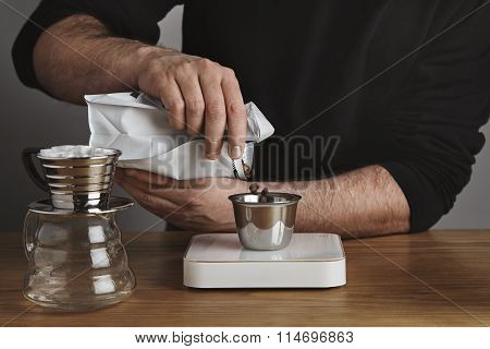 Brutal barista in black sweatshirt pours roasted coffee beans
