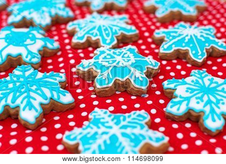 Many Snowflake Shaped Cookies On The Red Tablecloth.