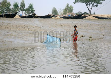 GOSABA, INDIA - JANUARY 19 : An unidentified fisherman uses fishing net in a traditional way for fishing in a Ganges river on January 19, 2009 in Gosaba, West Bengal, India.