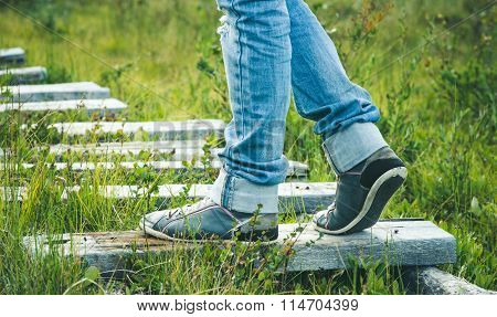 Woman Feet sneakers walking on wooden road Outdoor