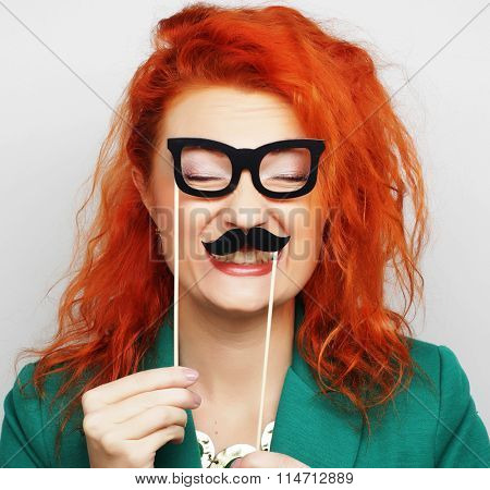 young woman holding mustache  on a stick.