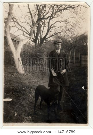 Vintage photo shows the boy with a dog on a walk