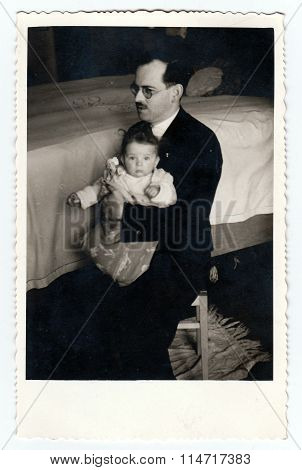 A vintage photo shows father with baby girl