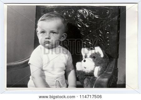 Retro photo of a small boy with teddy bear. Portrait photo was taken in photo studio