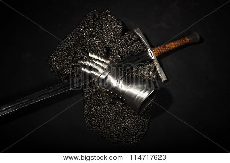 Medieval chain mail, iron gauntlet and a bastard sword still life