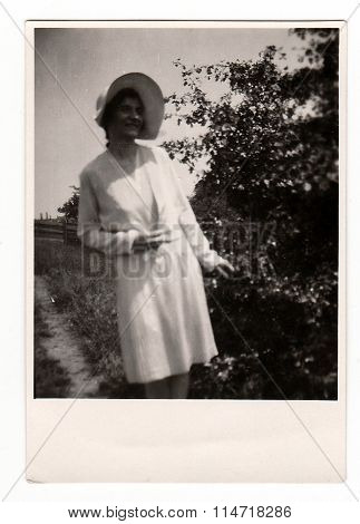 A vintage photo shows a young woman during a walk in nature