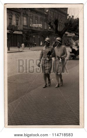 A vintage photo shows young women during a walk in the city