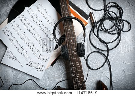 Electric guitar and headphones with music notes on grey background