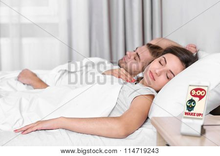 Happy couple waking up with mobile alarm clock