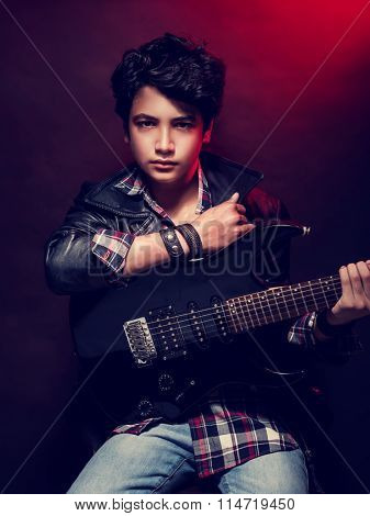 Talented serious teen boy with guitar over dark red background, playing on musical instrument, happy adolescence lifestyle