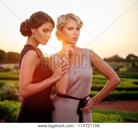 Two well-dressed woman in a beautiful park.