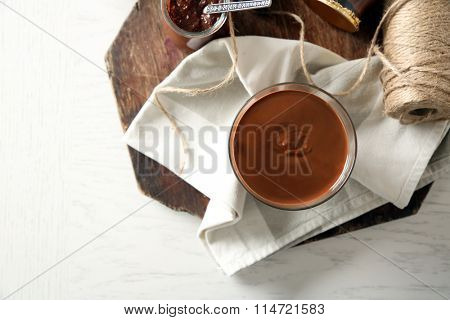Melted chocolate on glass bowl, on wooden background