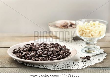 Chocolate morsels on wooden background