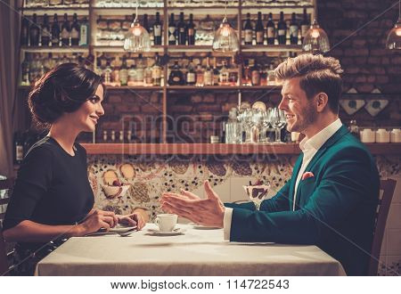 Stylish wealthy couple having desert and coffee together in a restaurant.