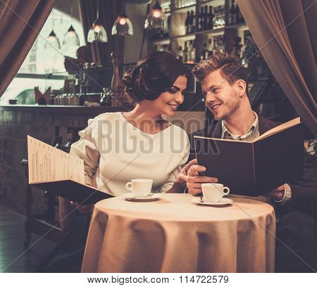 Stylish wealthy couple with menu in a restaurant.