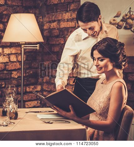 Waiter explaining the menu to a beautiful woman in restaurant.