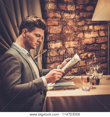 Stylish wealthy man with menu in a restaurant.