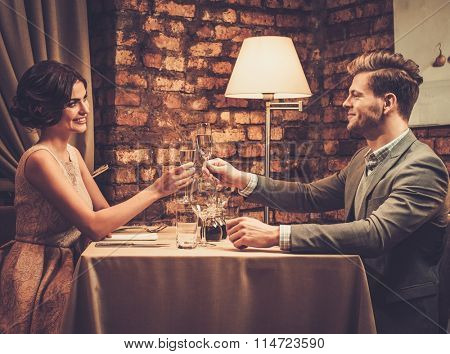 Stylish wealthy couple toasting with champagne in a restaurant.
