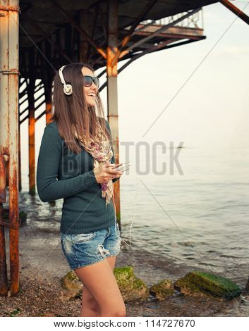 Happy smiling woman enjoy listening music with cameraphone against old pier near ocean.