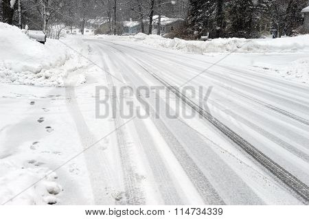 residential street after snow with tire tracks