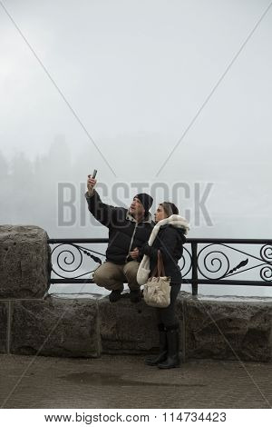 NIAGARA FALLS, CANADA-JANUARY 11, 2016:  Couple tourist doing a selfie at the horseshoe falls in Niagara falls, Ontario, Canada