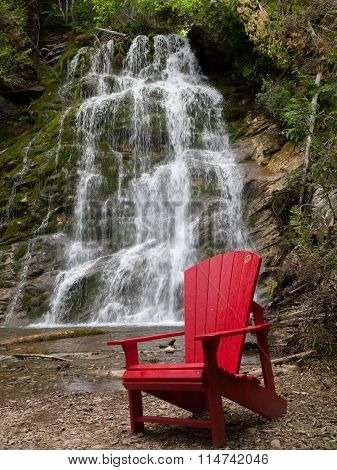 Red chair in front La Chute waterfall