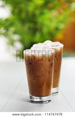 Cups of ice coffee on light blurred background