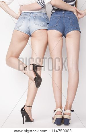 legs of young women, pair of butts in jeans shorts