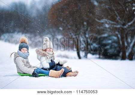 Little adorable girls enjoy a sleigh ride. Child sledding. Children play outdoors in snow. Family va
