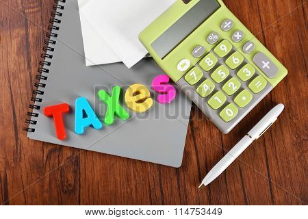 Alphabet TAXES and calculator with notebook on wooden table